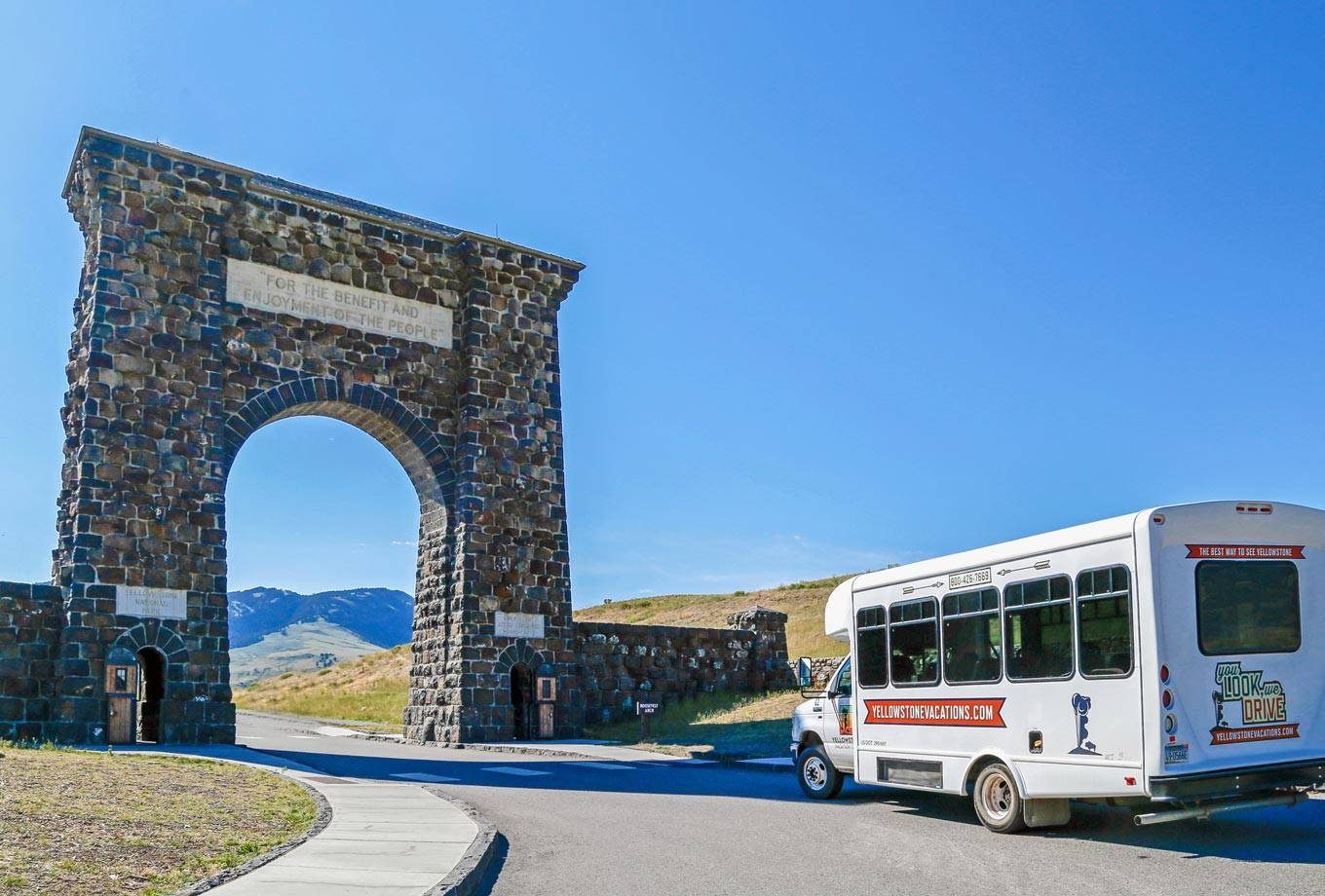 Yellowstone Vacation Tour bus from Gardiner, MT by the Roosevelt Arch at Yellowstone's north entrance
