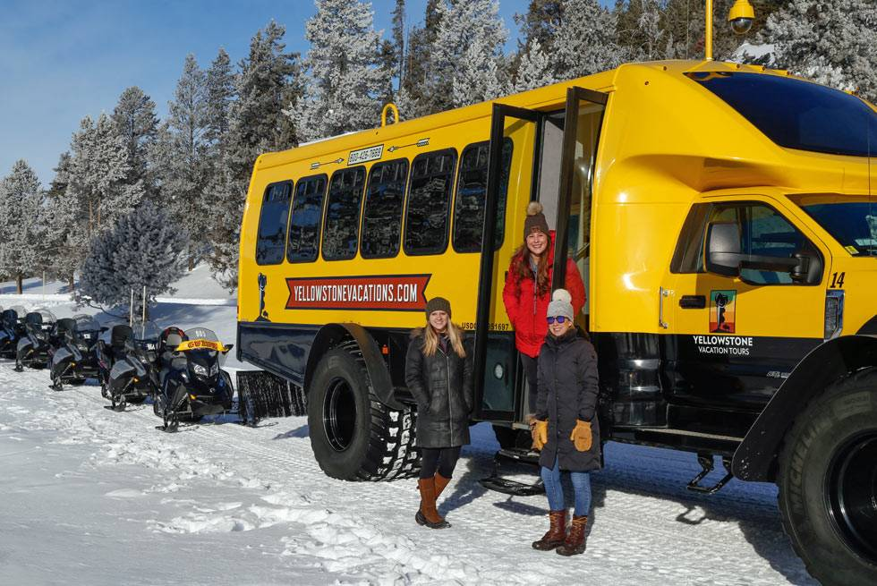 Three snowcoach riders pause for a photo during their Yellowstone tour