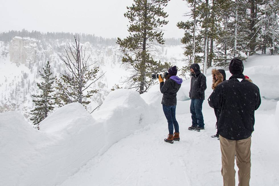 Snowcoach passengers stop to take some photos at the Grand Canyon of the Yellowstone.